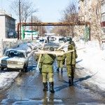 Russian conscripts carrying wooden boards down a street on Sakhalin.