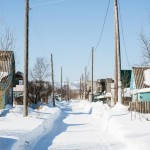 Colorful wooden homes line the snowy street in this village.