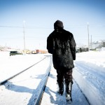 An elderly woman dressed in black walking her dog along the tracks in Sakhalin.