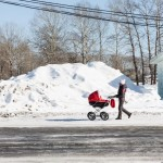 A woman walking her child along a road in Sakhalin. The snow is piled high on the side of the road.