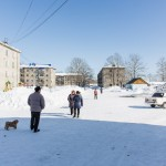 Stereotypical elements of a small Russian town : Lada, snow, grey Soviet housing, dog, babushka.
