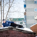 A Russian boy resting atop of a garage.