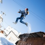A trail of snow falls from this boy's boots as he jumps off a roof.