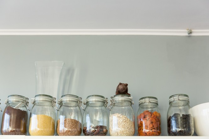 A toy mouse sitting atop the jar with oatmeal. Dried fruit for breakfast are to the right of the oatmeal.