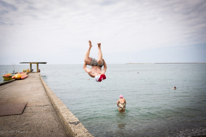 Russian youth doing a backflip into the water on the Sochi shore.