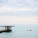 Russians swimming in the Sochi waters as a parasail goes by in the background.