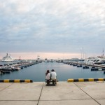 A Russian couple sitting in front of the Sochi Harbour at Sunset.