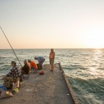 Russians fishing off a pier in Sochi at sunset.