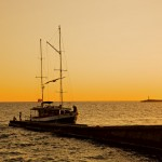 Summer sun setting over Sochi waters as a boat docks.