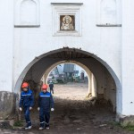 Construction workers passing through a gateway inside the Solovetsky Monastery. A photo of Jesus hangs above them.