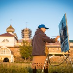 A Belarusian girl painting in front of the Solovetsky Monastery during sunset.