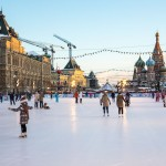 The setting sun throws its last rays on GUM department store as children ice skate on Red Square.
