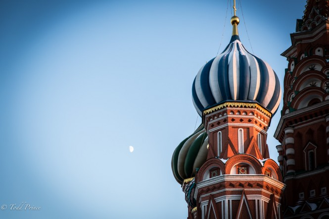 The moon looks down on St. Basil's Cathedral as snow clings to the cupola.