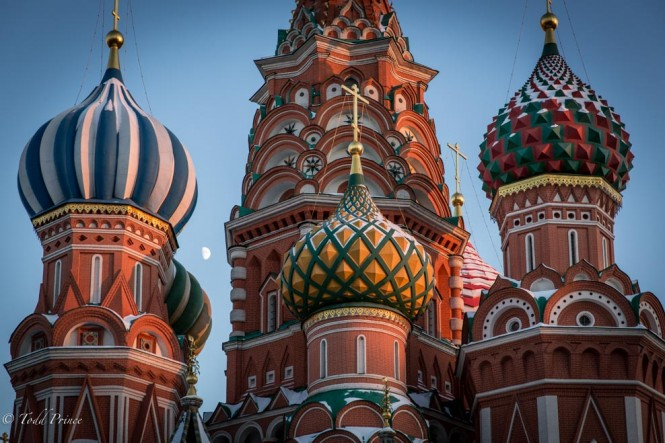 The moon peaks out between the cupolas on St. Basil's Cathedral.