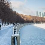 Two students walk along the Moscow River, their backs to the city's Financial District.