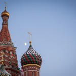 A plane flies over St. Basil's cathedral and the moon shines between its cupolas.