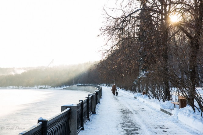 A Russian woman walks her dog along the Moscow River on a cold but sunny Moscow winter day.