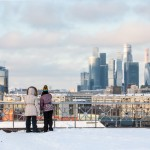 A mother and daughter look out upon Moscow's Financial District amid a walk on a sunny day.