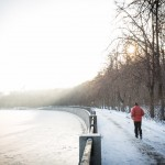 A man jogs along the Moscow River as the sun peaks through the trees.