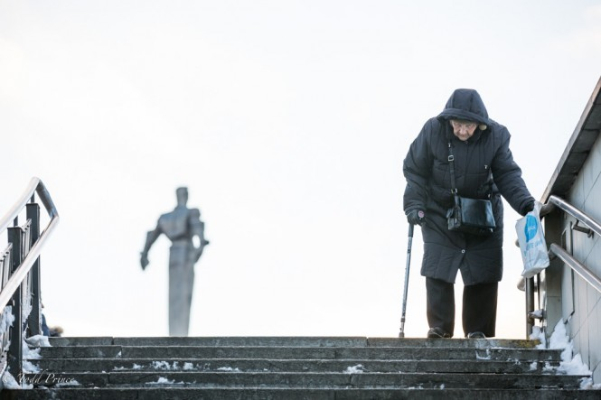 An elderly woman walks down stairs as Gagarin statue rises behind her.