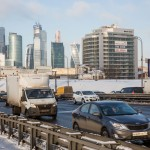 Cars pass along a major city road as Moscow's Financial District basks in the sunlight in the background.