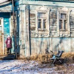 A young girl stands in front of a home in the village of Perovo.