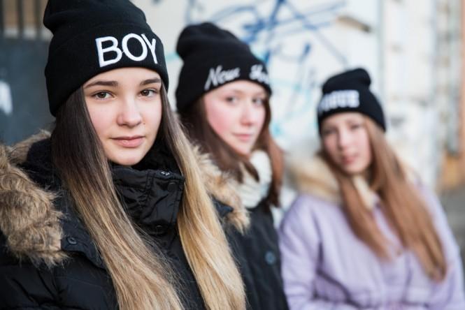 Three Vladivostok teenagers sporting trendy black winter hats.