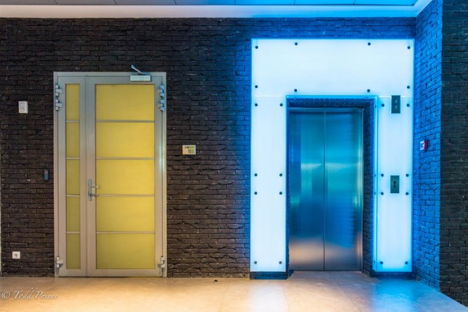 A blue-neon light highlights the elevator entrance on the 3rd floor.