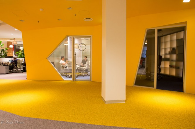 A meeting room on the right. Notice the creative shape of the windows, bright yellow color and green plants (far left).