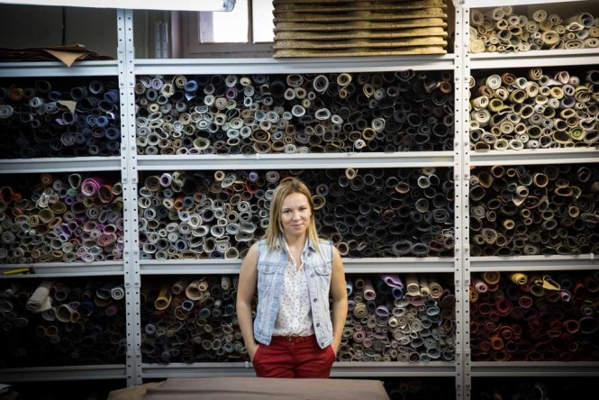 Anya, a shoe maker, standing in the factory room where she buys colored leather from Europe.