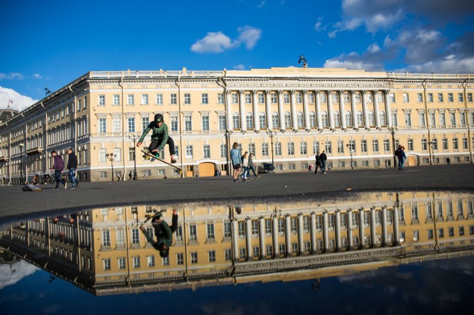 A skateboarder's reflection is captured in the water on Palace Square