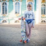 A young Russian girl skating on a long board with a NY sweater in front of the Hermitage.